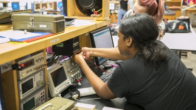 student working on electronic equipment