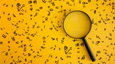 A magnifying glass on a yellow background with floating letters
