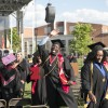 man excitedly waving his hand during graduation ceremony