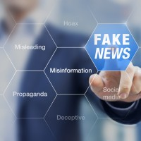 """man pointing to various words including """"fake news, misinformation, misleading"""""""