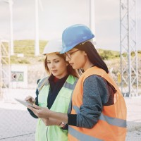 women standing on construction site reading from clipboard