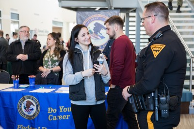 A student speaking with a police officer in the Student Success Center