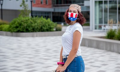 female student standing in front of Student Success Center wearing facemask