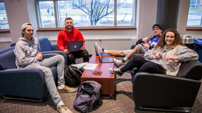 four students sitting on couches smiling