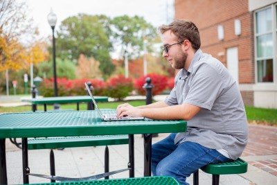student sitting outside in front of laptop